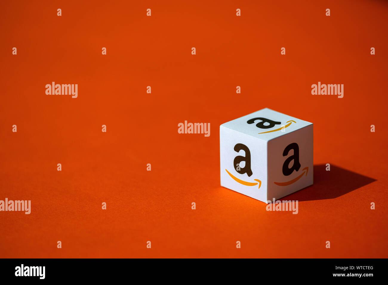 Kiev, Ukraine - le 10 septembre 2019: un coup de papier imprimé cube avec le logotype de la société Amazon, qui a placé sur un fond orange. Banque D'Images