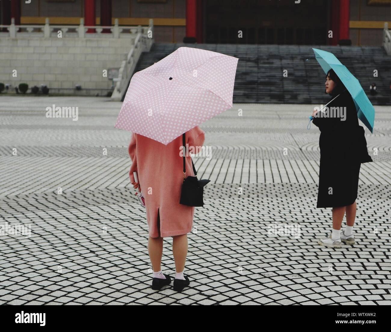 La femme debout avec des parasols sur sentier à Chiang Kaishek Memorial Hall Banque D'Images