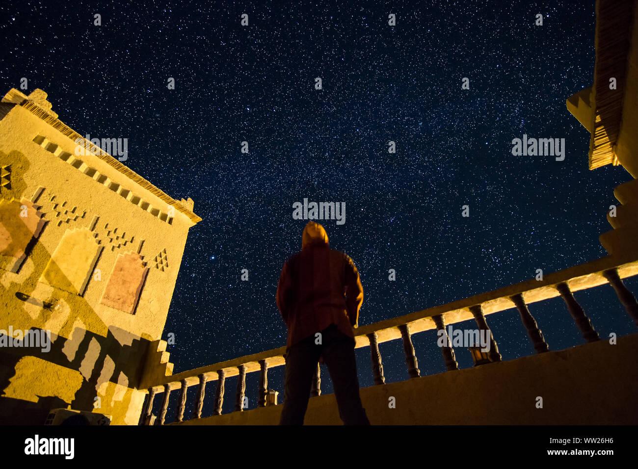 Un homme debout regardant le ciel étoilé sur le toit d'une kasbah dans le sud du Maroc. L'astrophotographie Banque D'Images