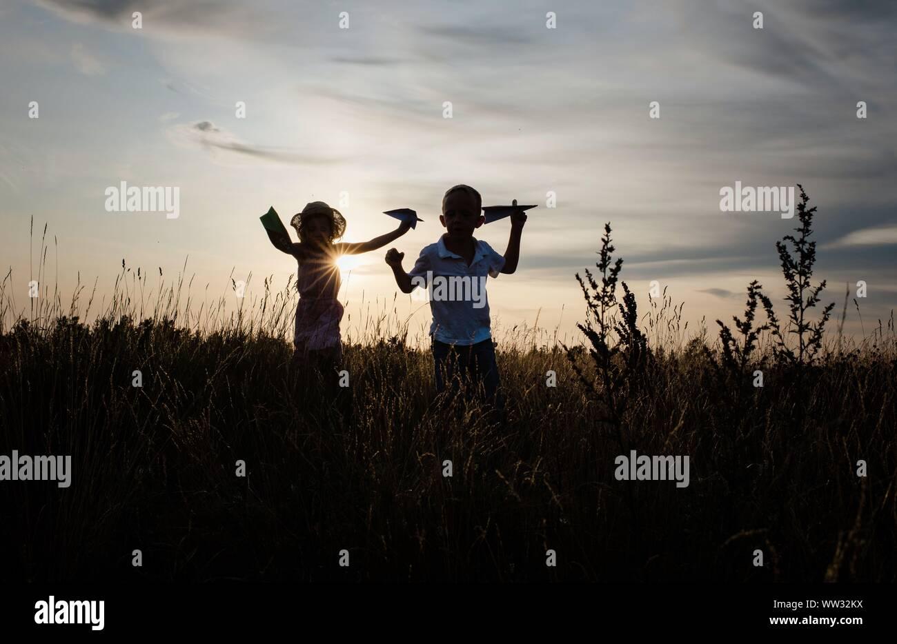 Frères et sœurs jouer dehors dans un pré au coucher du soleil en été Banque D'Images
