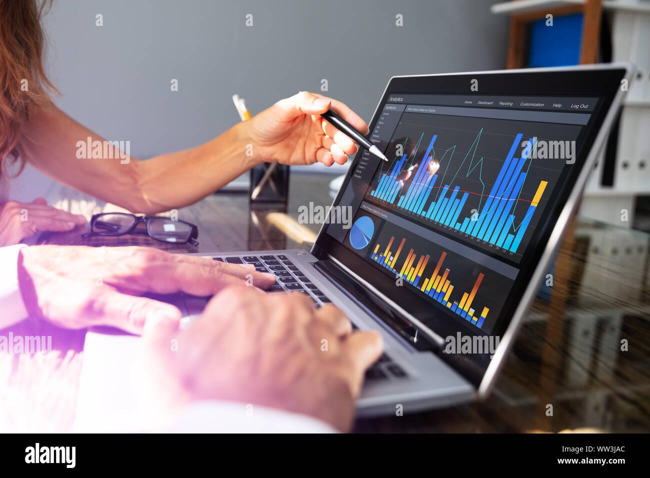 Close- Up d'employés de bureau de l'analyse graphique sur ordinateur portable avec son collègue. Banque D'Images