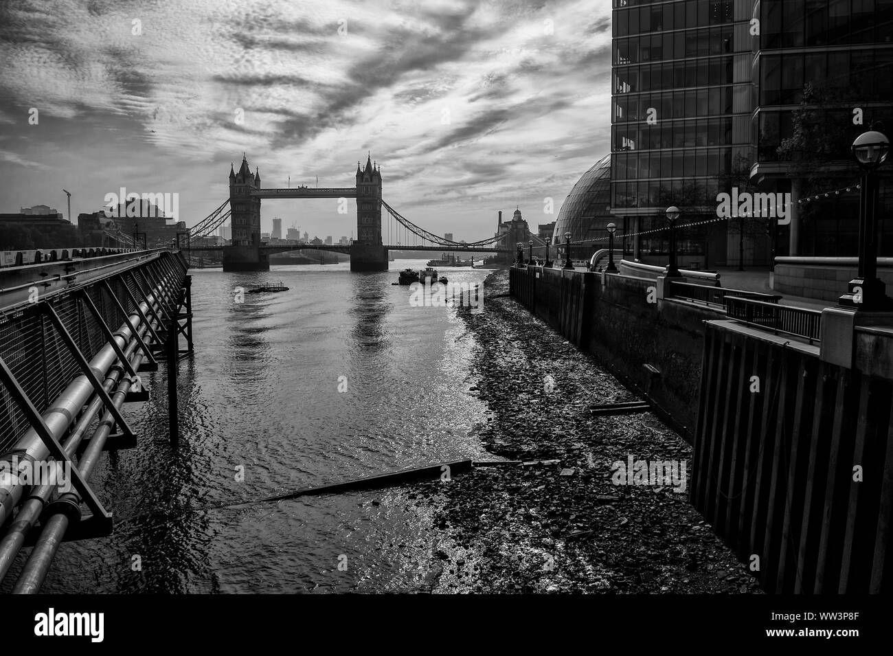 Silhouette monochrome classique vue sur le Tower Bridge à partir de la rive sud de la Tamise sur une marée basse matin à Londres, Angleterre, RU Banque D'Images
