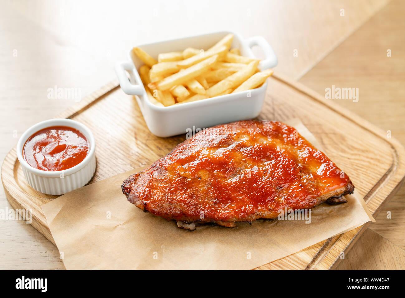 Côtelette de porc barbecue. Côtes de porc grillées avec bébé sauce barbecue épicée servis avec frites. Banque D'Images