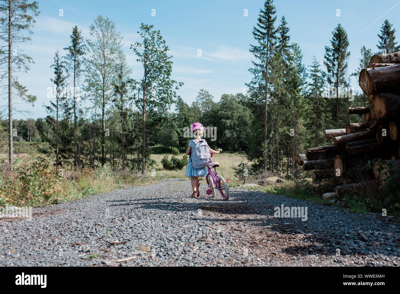 Jeune fille qui marche à la maison de l'école avec son vélo dans la campagne Banque D'Images