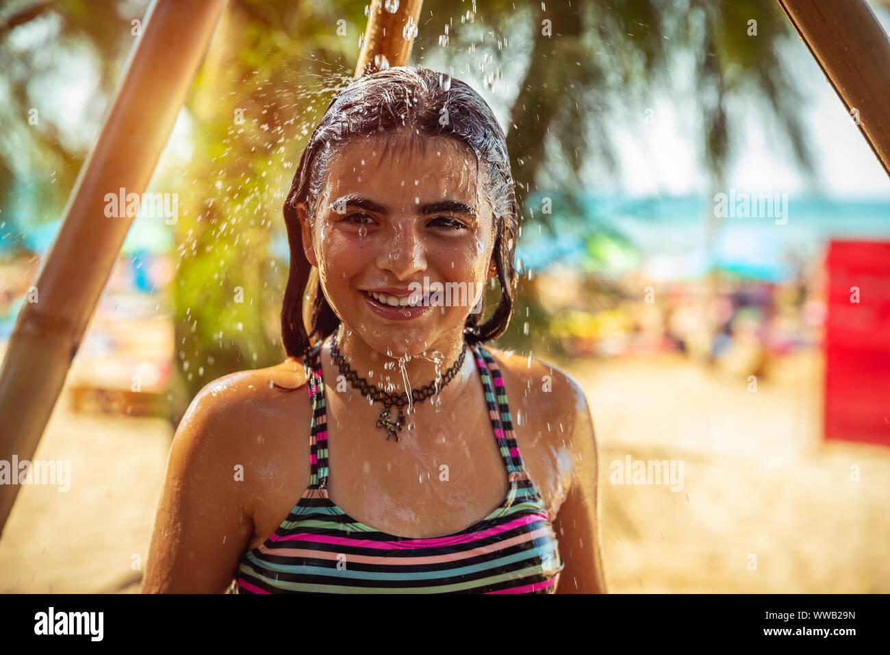 Portrait d'une magnifique petite fille sur la plage resort, enfant heureux de prendre douche sur la plage, s'amuser en plein air, profitant des vacances d'été Banque D'Images