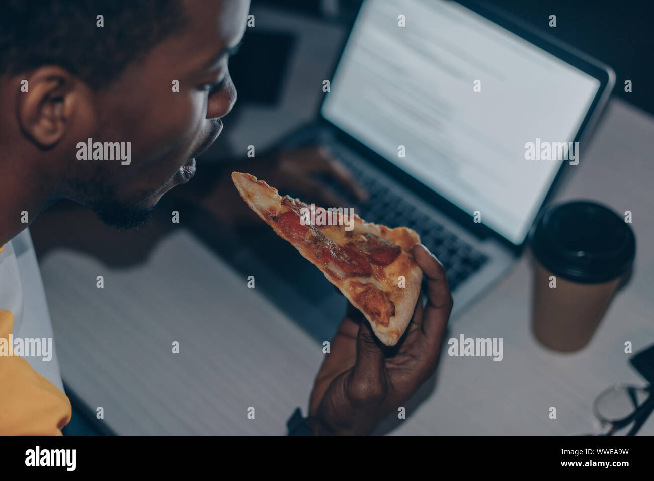 Young african american programmer eating pizza tout en travaillant de nuit in office Banque D'Images
