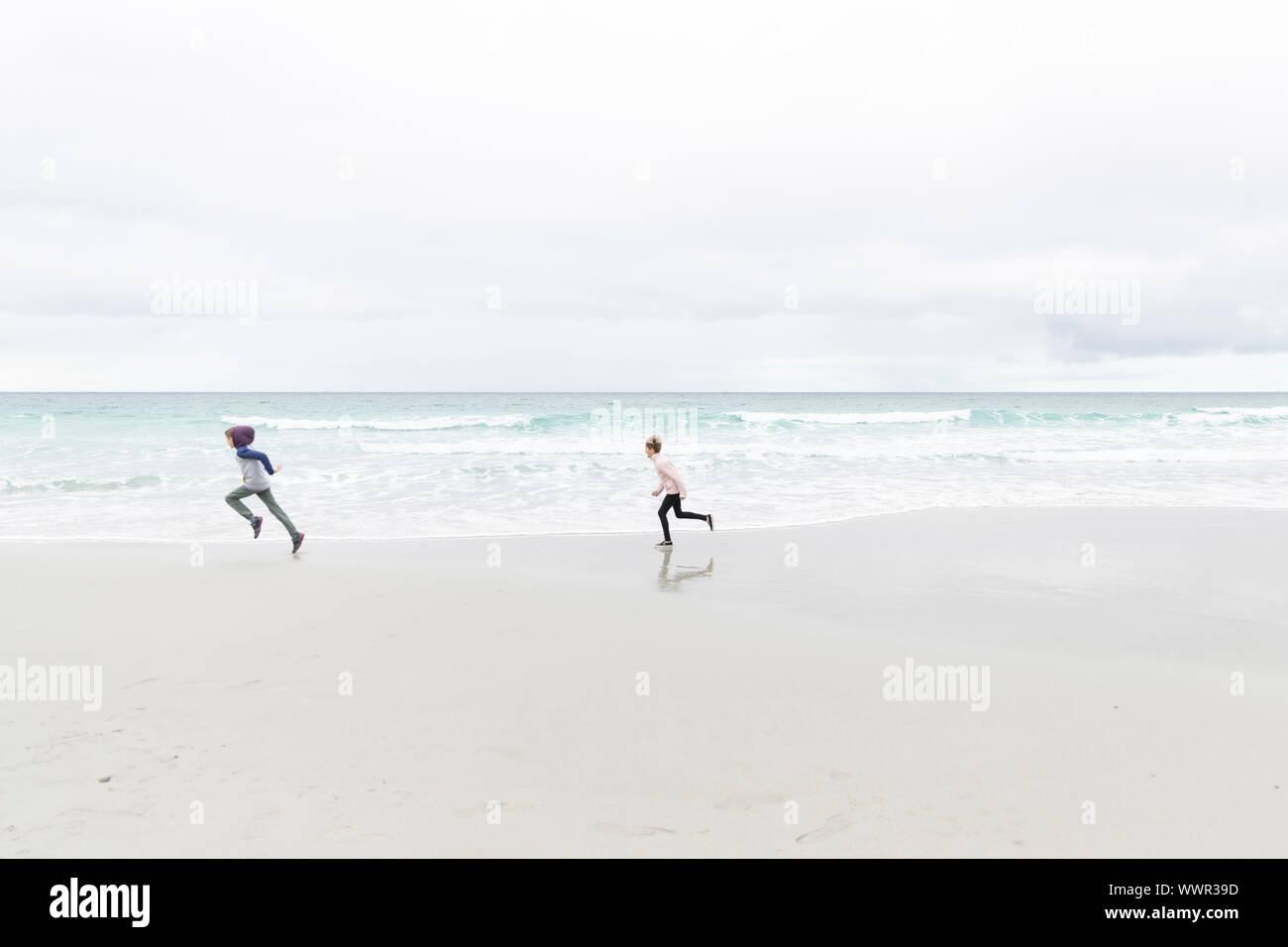 Jeune garçon et fille courir sur la plage de Carmel, Californie Banque D'Images