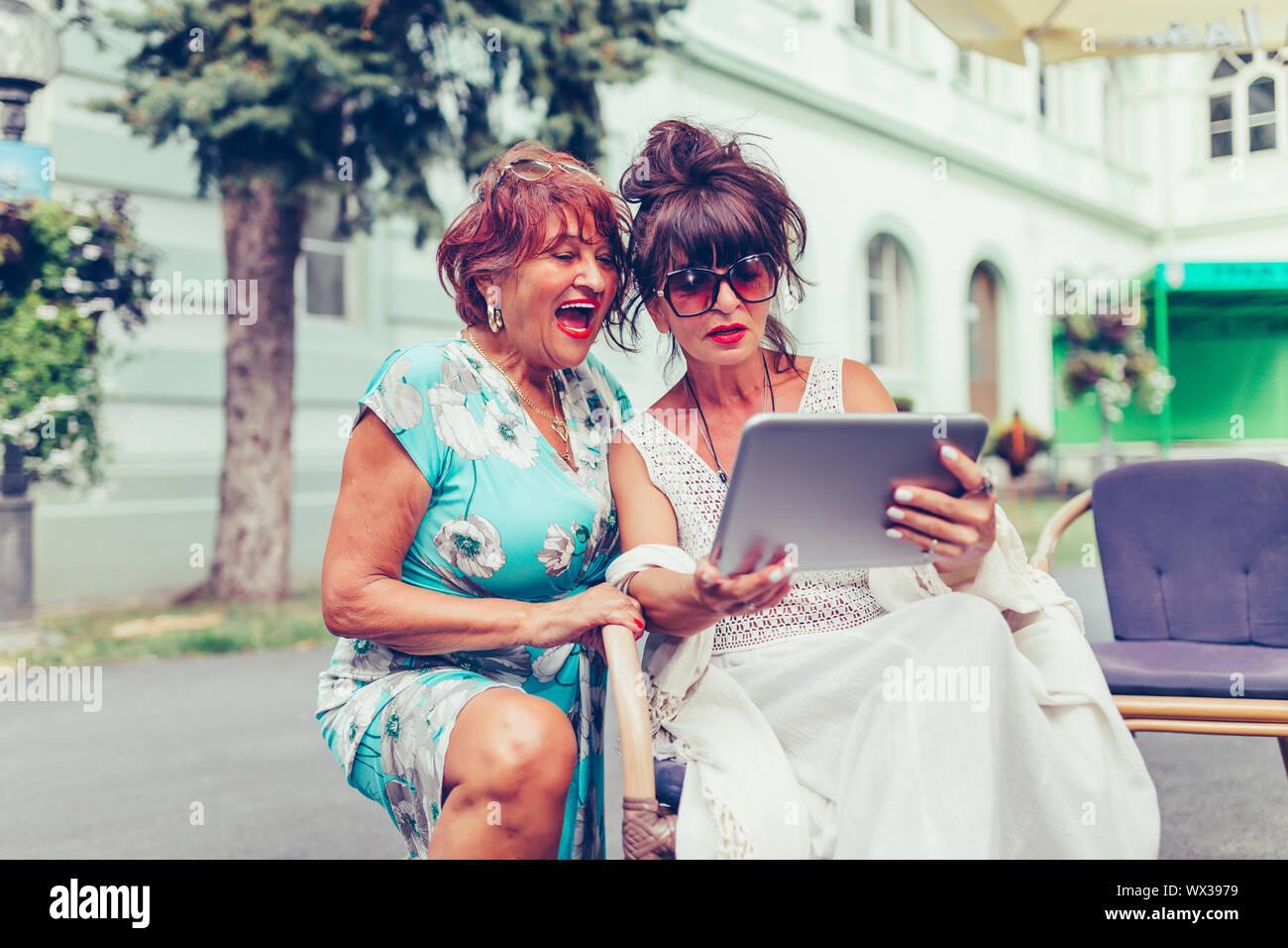 Deux senior women sitting in outdoor cafe en riant et en regardant les médias sociaux et drôles de vidéos virales sur une tablette. Banque D'Images