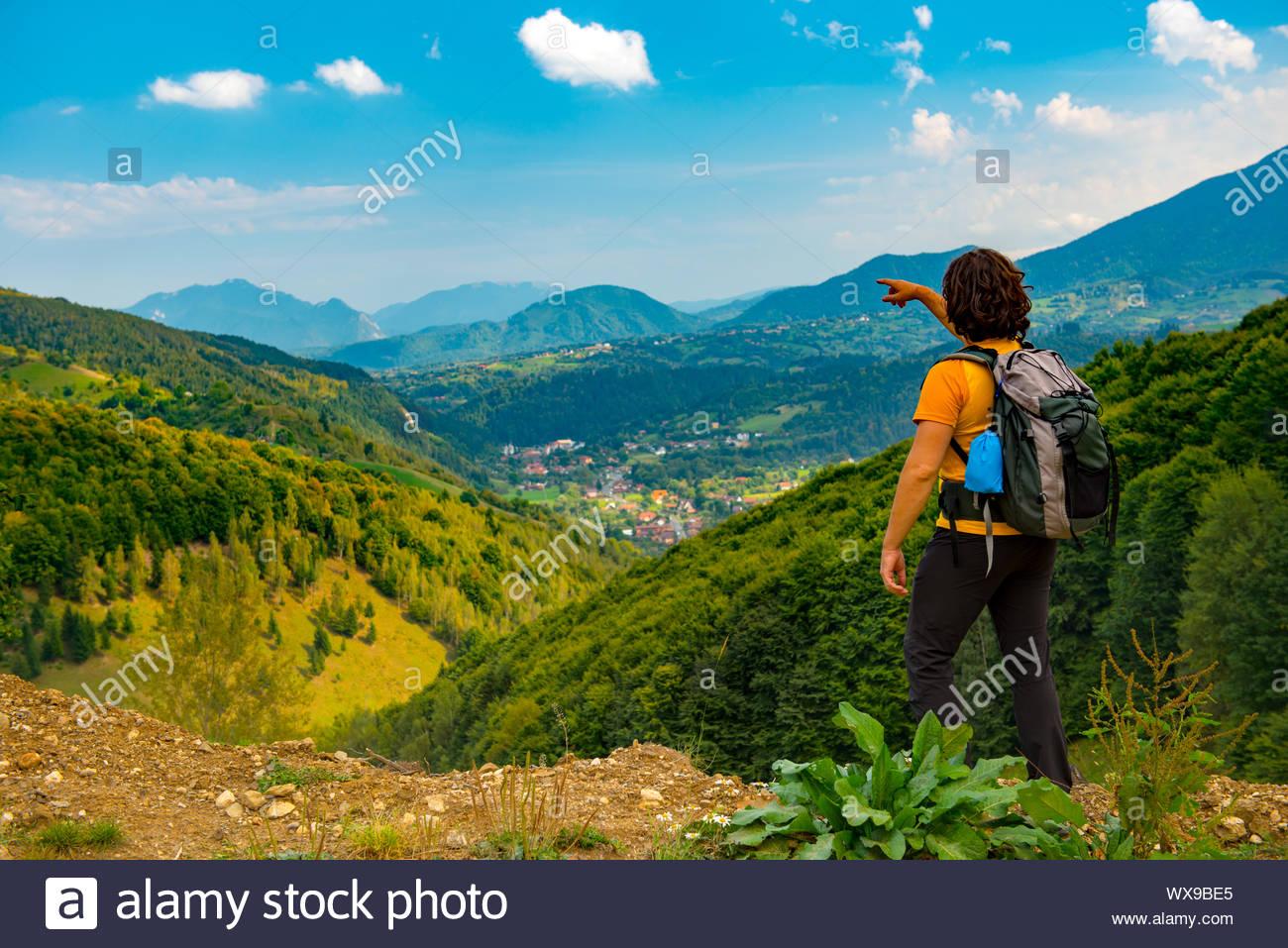 Jeune randonneur pointant vers un beau paysage de montagnes couvertes de forêts. Randonnée dans un beau jour d'été. Banque D'Images