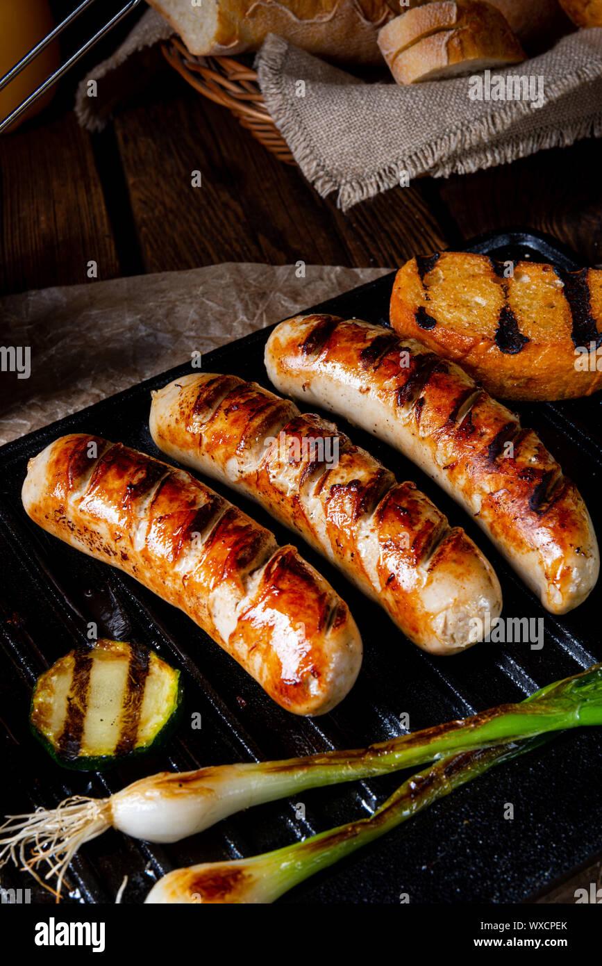 De délicieuses saucisses grillées avec divers légumes grillés Banque D'Images