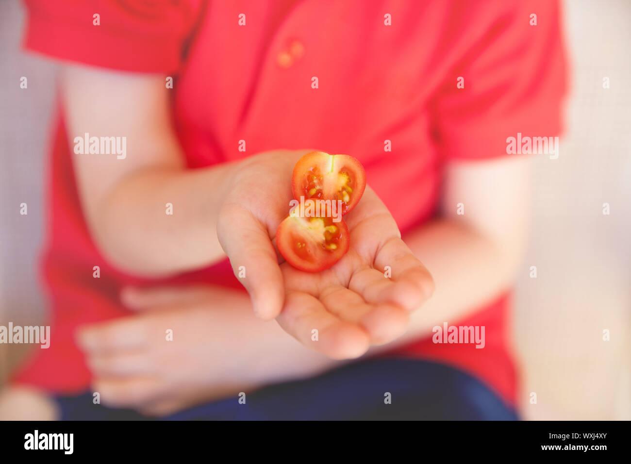 Garçon tenant une moitié de tomate cerise Banque D'Images