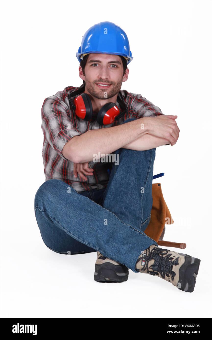 Artisan avec un casque et des bouchons d'assise sur le sol Banque D'Images