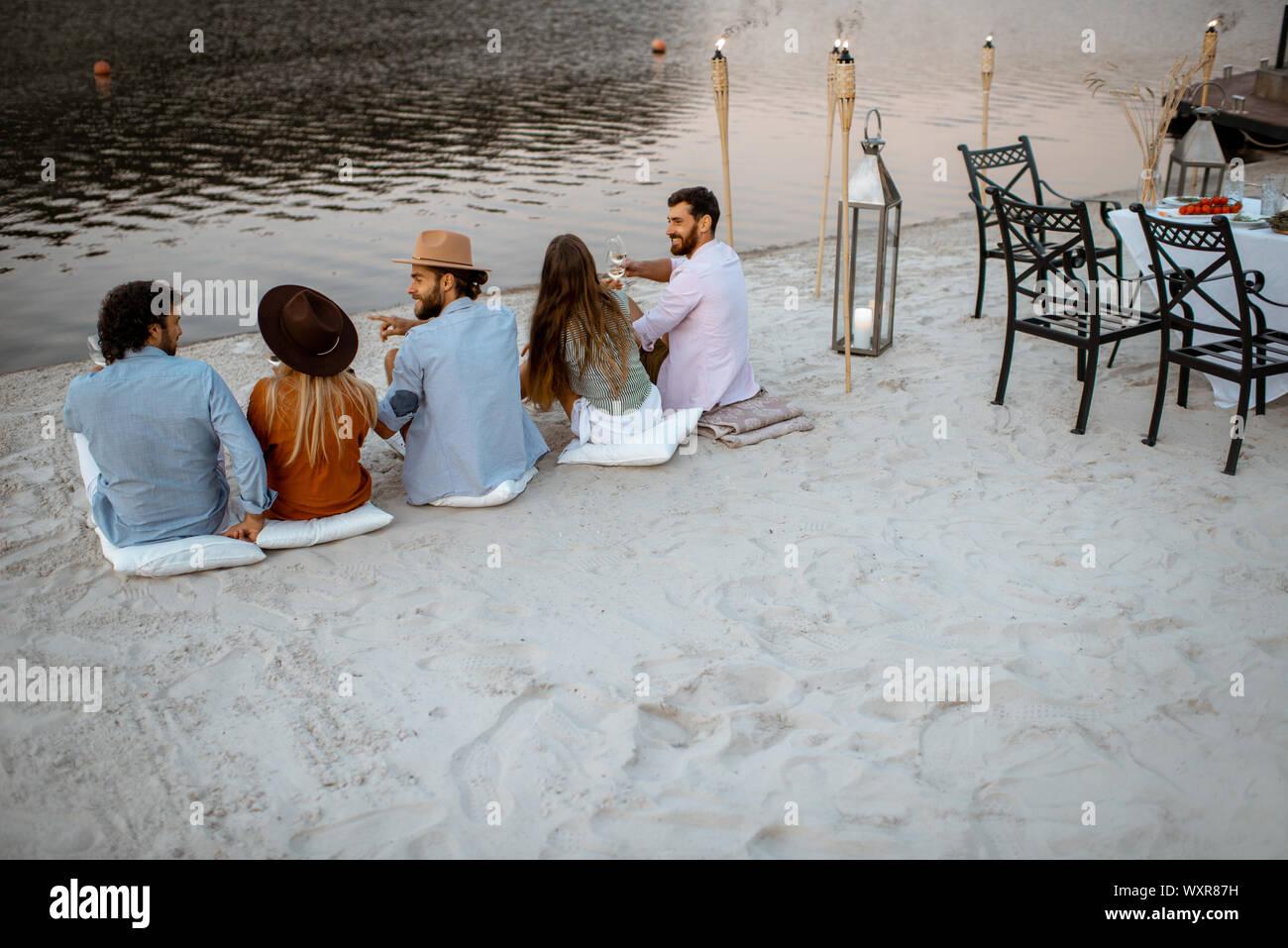 Groupe de jeunes amis assis sur la plage, profiter du temps ensemble le soir au cours d'une réunion festive et le dîner en plein air Banque D'Images