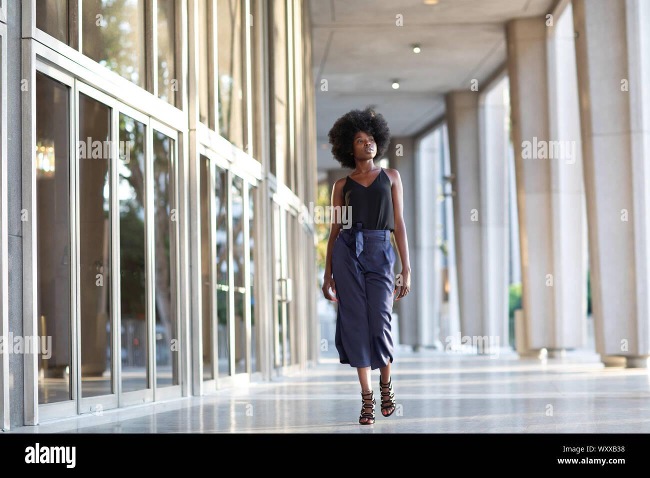 Une jeune femme à la mode de marche avec assurance dans le couloir à l'extérieur de l'édifice financier Banque D'Images