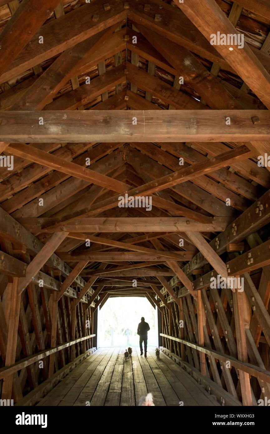 Poutres en treillis et des formes géométriques et man walking dogs à l'ancien pont, pont couvert par Sheffield Plain, Massachusetts. Banque D'Images
