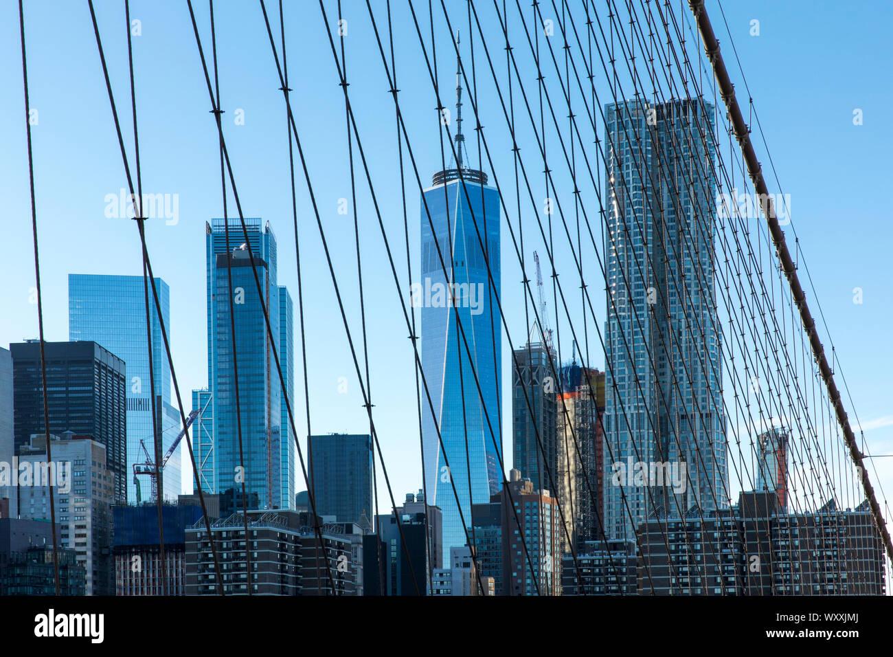 Gratte-ciel de Manhattan vue par l'intermédiaire du fil prend en charge et les câbles du pont de Brooklyn, New York City Banque D'Images