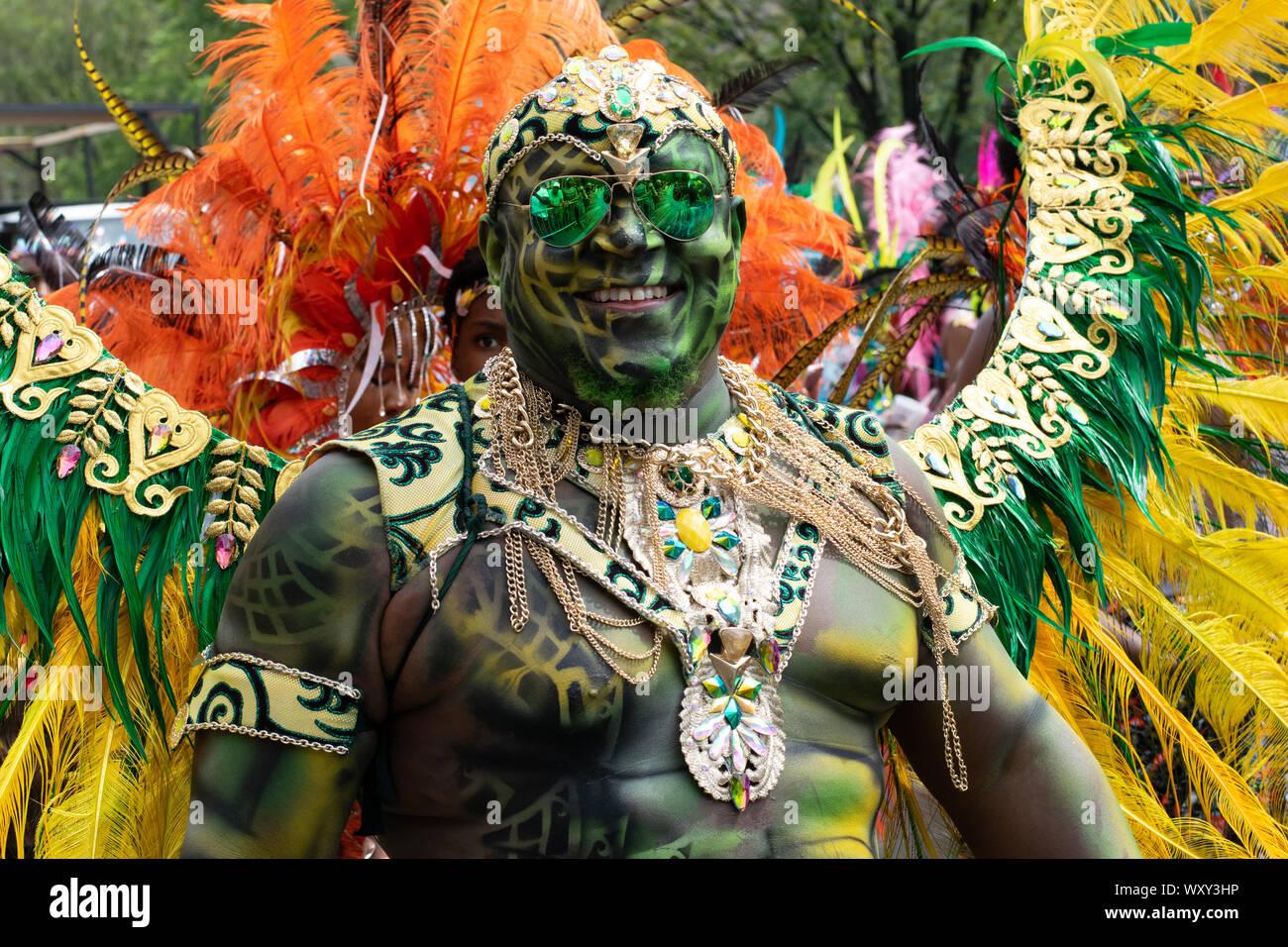 Stolz auf seine Körperbemalung blickt der Teilnehmer ein West Indian Day Parade à New York City dans Die Kamera. Auf dem Rücken trägt er Federschmuck. Banque D'Images