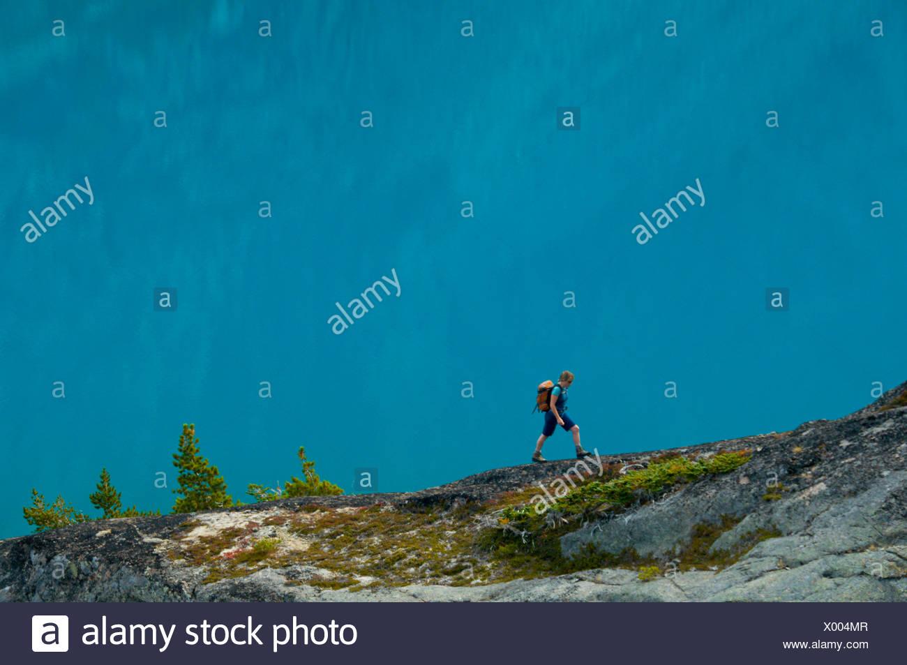 Randonnées d'une jeune femme en face d'un lac bleu dans la gamme Niut, British Columbia, Canada Banque D'Images