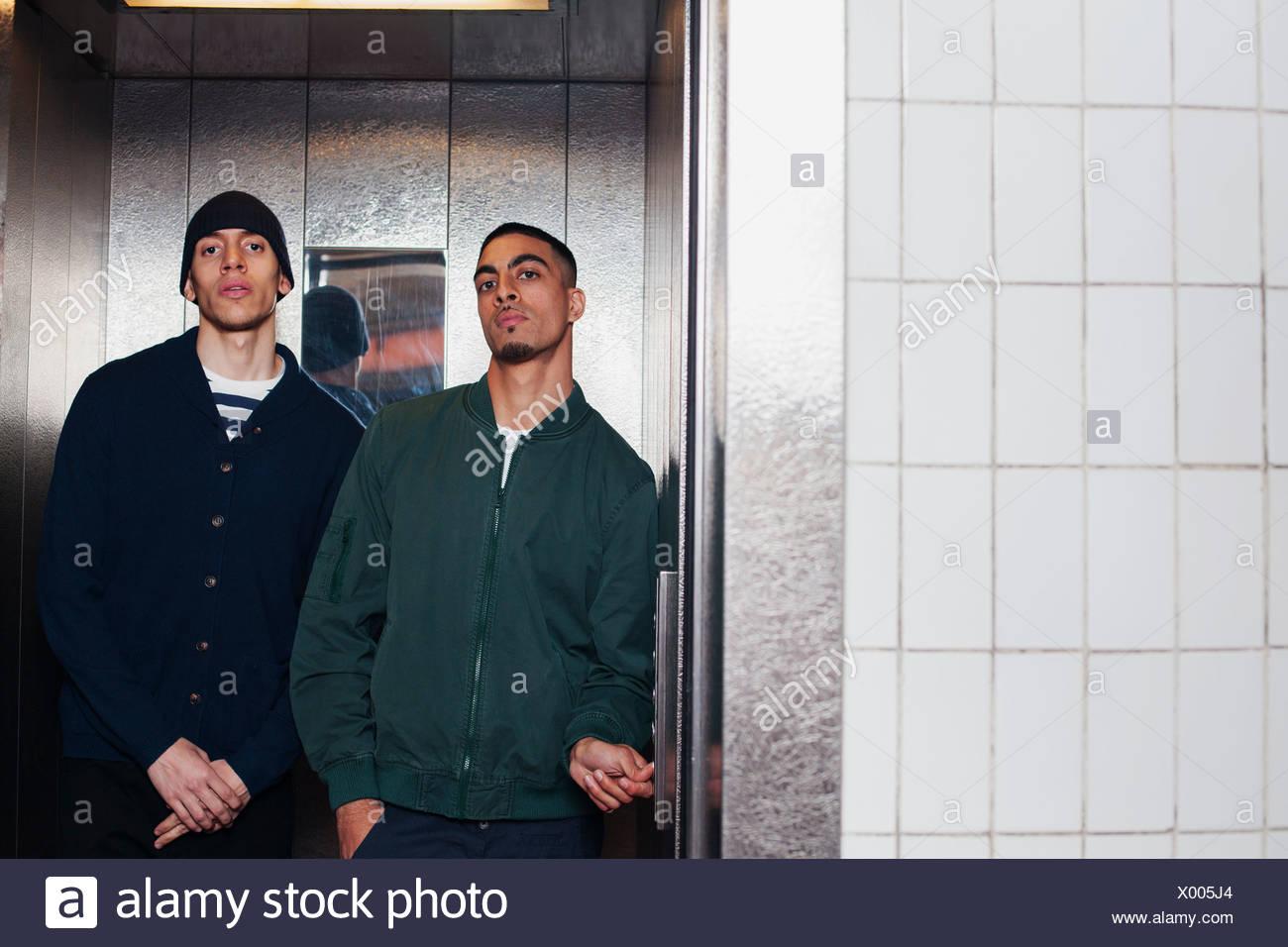 Les jeunes hommes en ascenseur Photo Stock