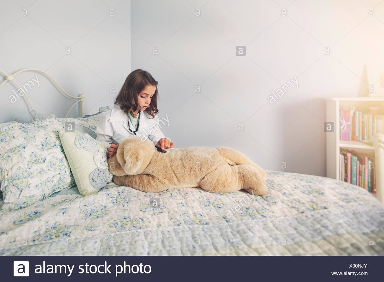 Girl dressed up in lab coat assis au lit en utilisant le stéthoscope soft toy Photo Stock