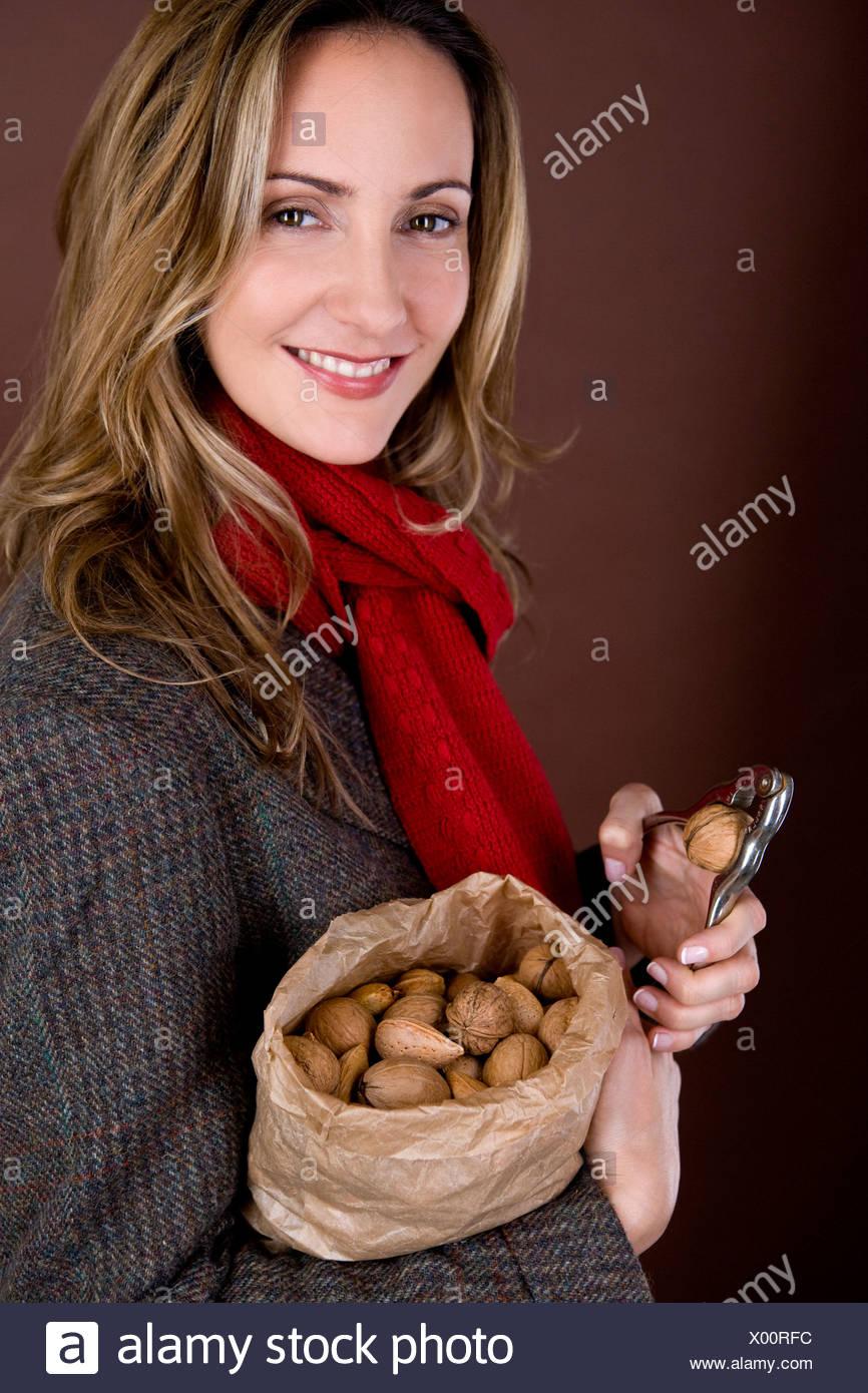 A mid adult woman la fissuration d'un écrou Photo Stock