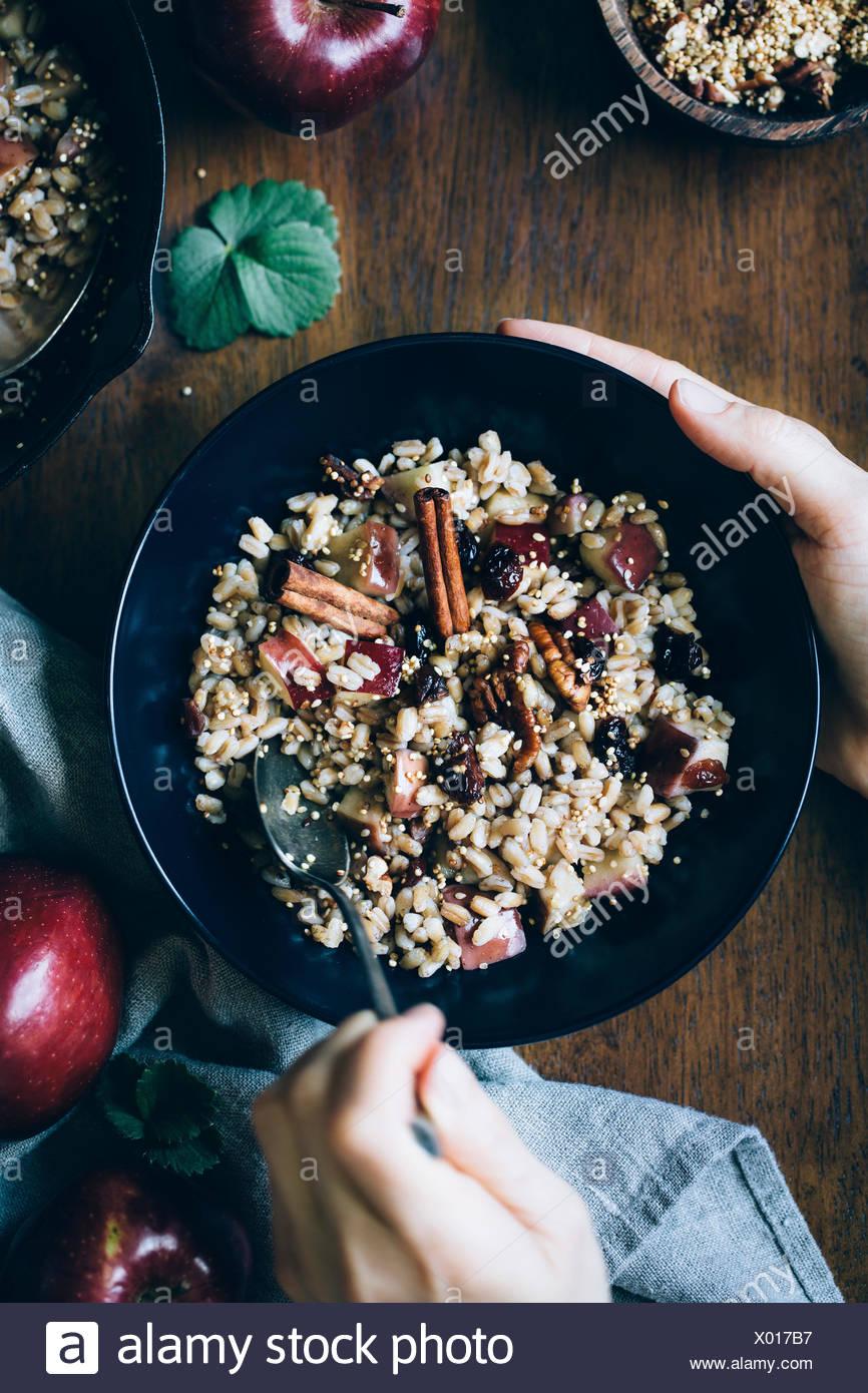 A womans mains sont photographiés comme elle est sur le point de manger un bol de petit-déjeuner chaud Farro bol avec des pommes à la cannelle. Photo Stock