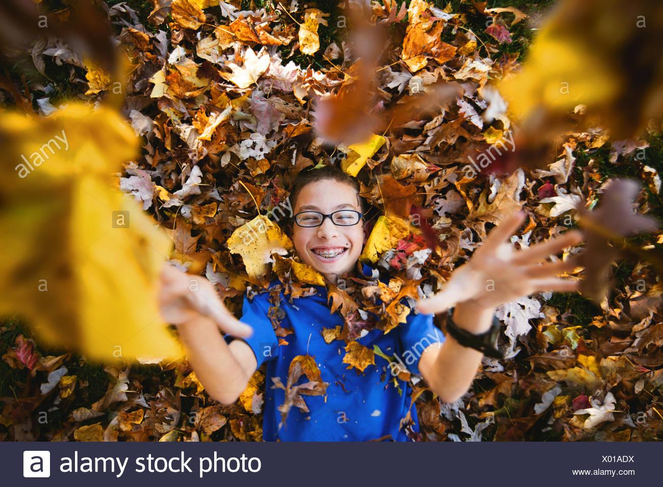 Garçon allongé sur le dos jouant avec des feuilles d'automne Banque D'Images