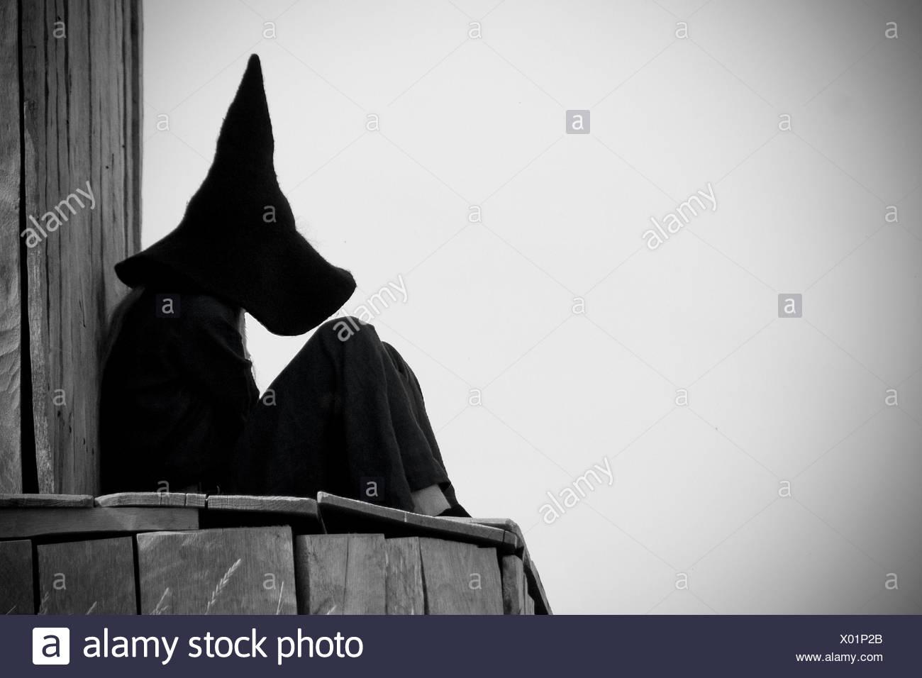 Vue latérale d'une sorcière Halloween assis contre le Ciel clair Photo Stock