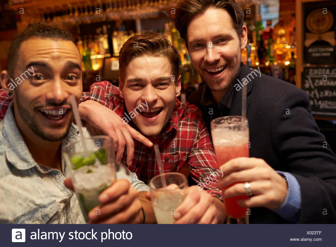 Réunion d'amis masculins pour prendre un verre en soirée au bar à cocktails Photo Stock