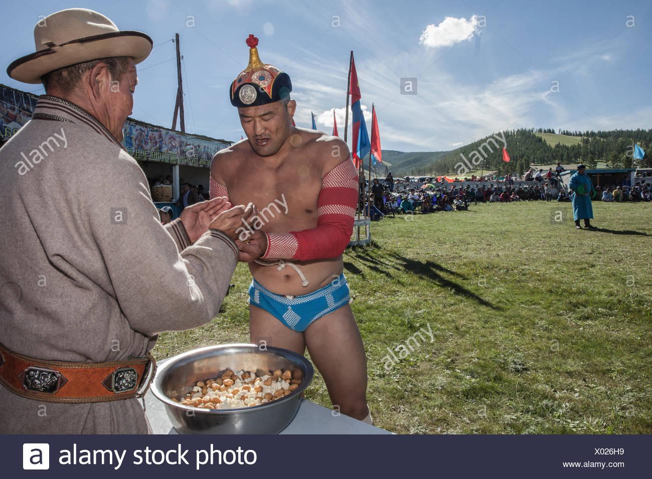 Un lutteur Mongol, plein de fierté, attrapant une poignée de fromage qu'il va jeter dans le ciel et la foule de ses admirateurs. Lantern Festival annuel à Tsetserleg, province Arkhangai, Mongolie Banque D'Images