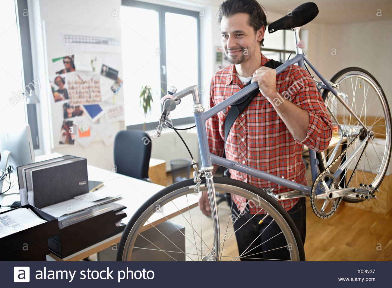 Germany, Cologne, young man carrying bicycle, smiling Photo Stock