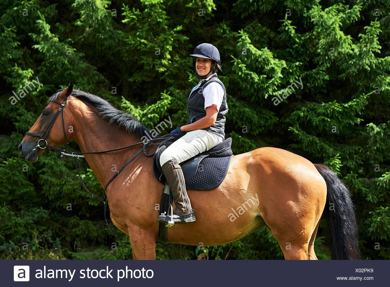 Vue latérale du young woman wearing hat équitation à cheval et des bottes à la caméra en souriant Photo Stock