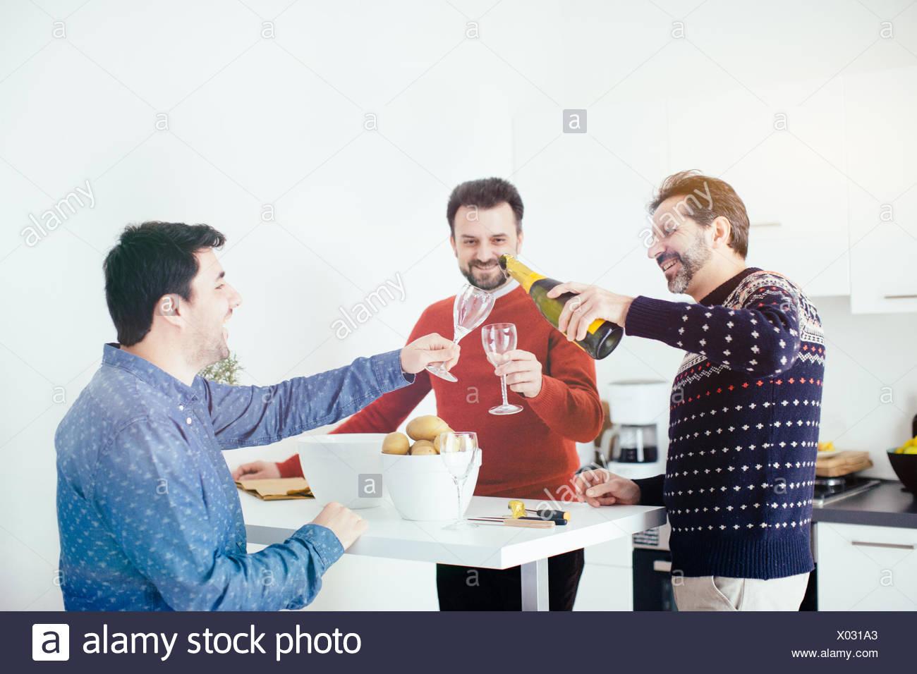 Men enjoying champagne tandis que dans la cuisine fait peler Photo Stock