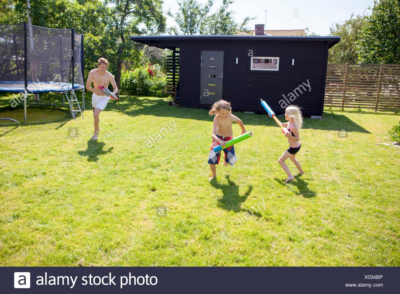 Frères et sœurs (8-9, 10-11) jouant avec les pistolets à eau dans la cour Photo Stock