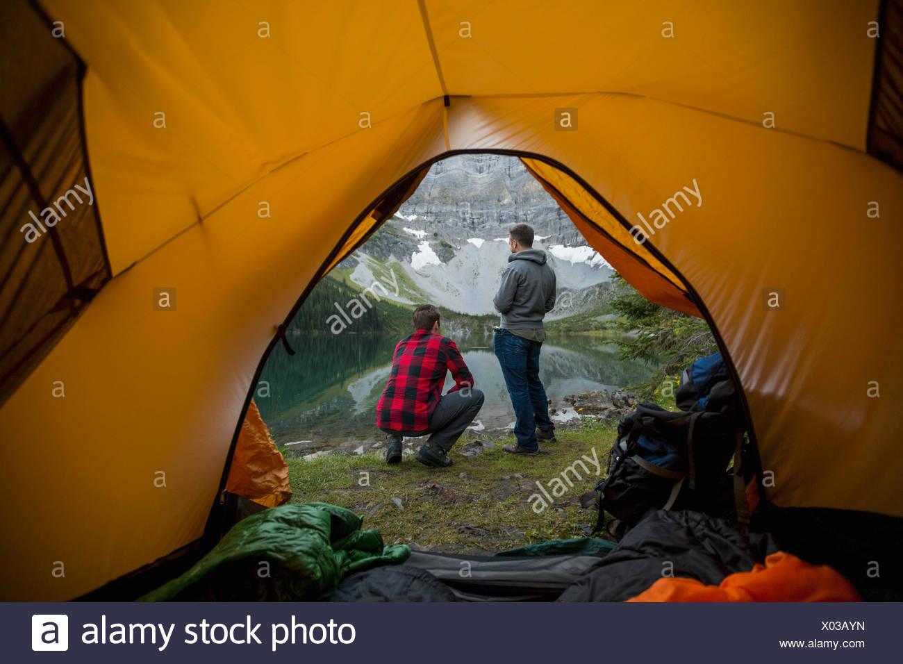 Les hommes à la vue sur le lac à l'extérieur de tente de camping Banque D'Images