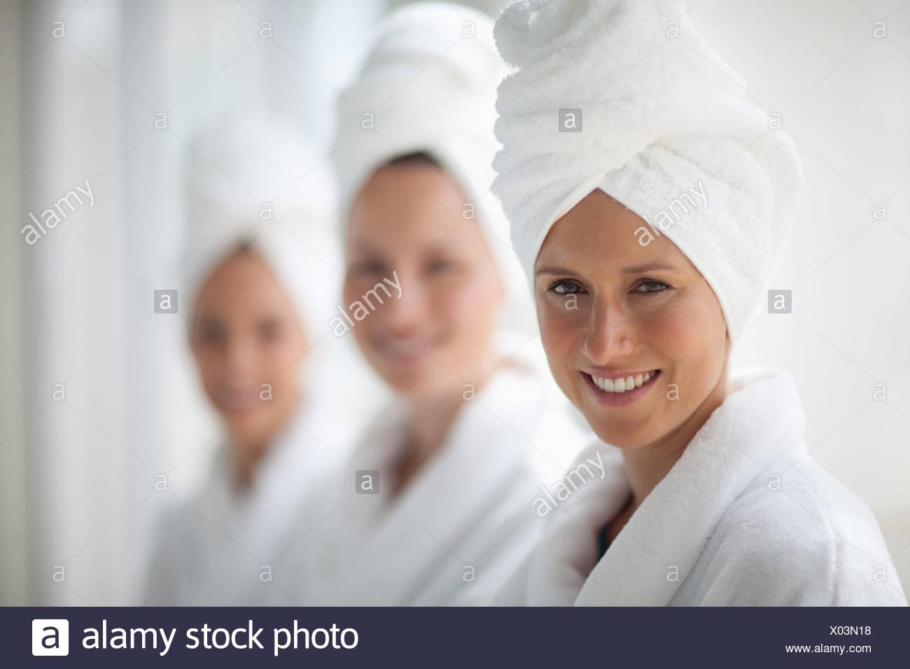 Portrait of smiling women in peignoirs et sèche enveloppée dans des serviettes de bain Photo Stock