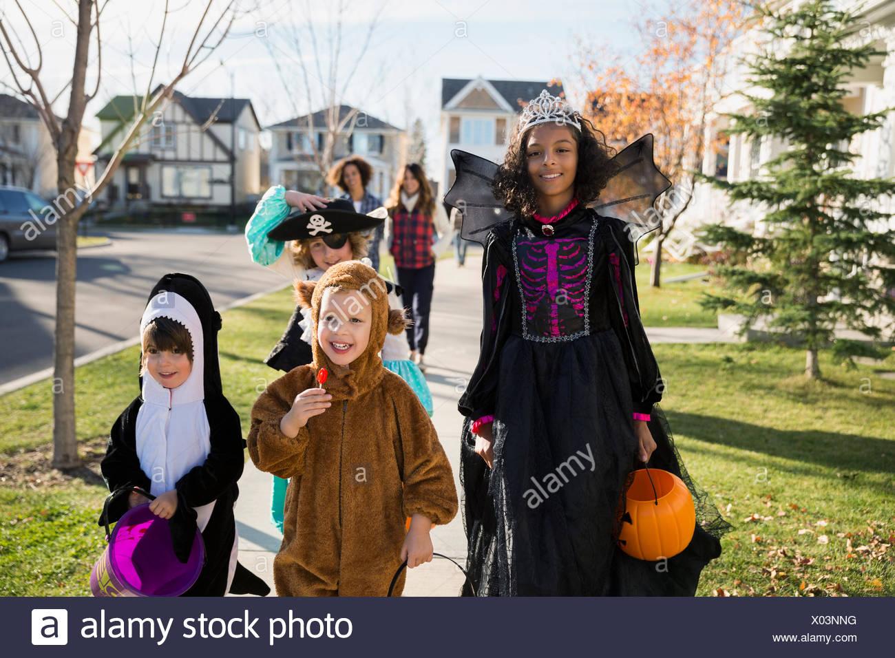 Les enfants en costume d'Halloween sur trottoir quartier Photo Stock