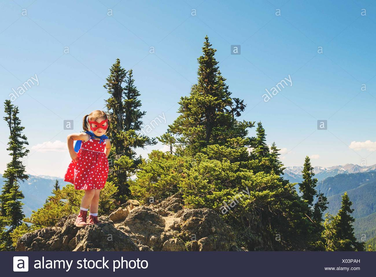 Jeune fille (2-3) wearing super hero masque et cape debout sur la montagne de Photo Stock