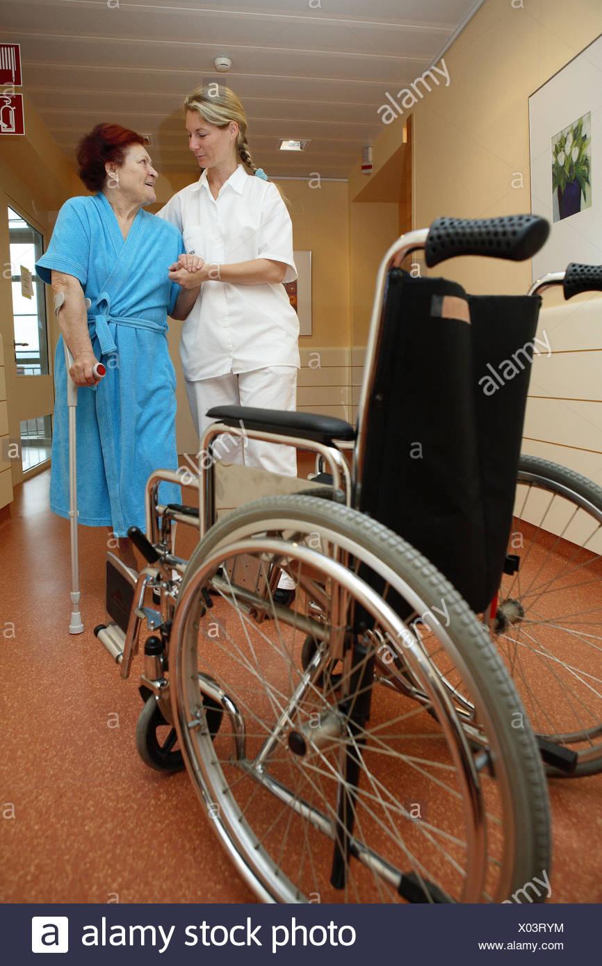 Clinique, hall, physiothérapeute, patient, senior, béquilles, besoin de soins, de plomb, de l'aide, à la pratique, le contact oculaire, l'invalide en fauteuil, de la médecine, de la station de la personne malade, une maison de soins infirmiers, l'occupation, hall de la clinique, les soins infirmiers, les professions, les femmes, les deux, des personnes âgées, des soins infirmiers-misère, vieux, peignoir, infirmière, infirmière, infirmière de la force, du personnel infirmier, la pratique, former, soutenir, support, aide, soins, allocations, l'accompagnement, de soins, de convalescense, l'accompagnement, la guérison, la réadaptation, l'ensemble du corps, à l'intérieur, Photo Stock