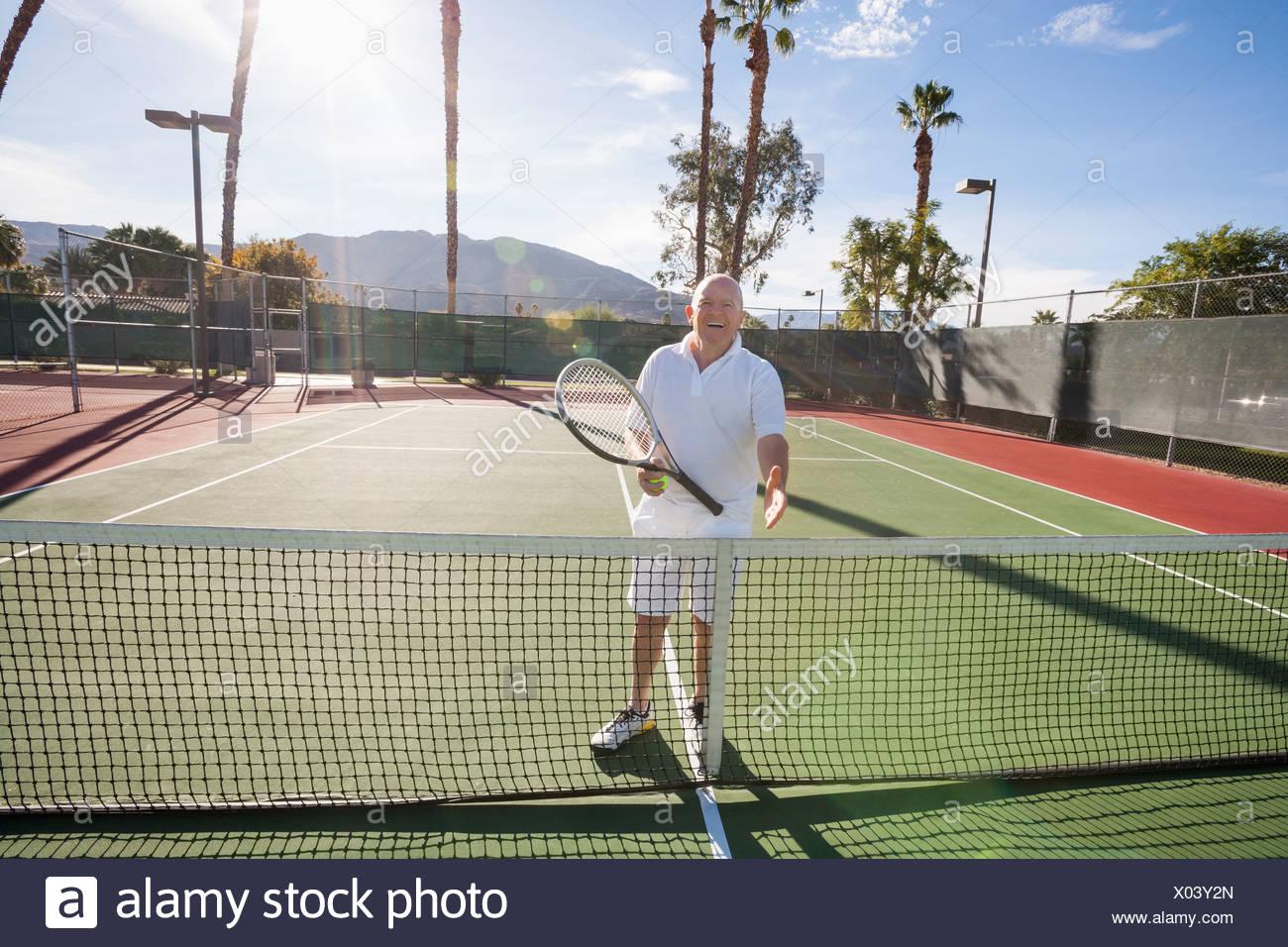 Portrait de senior tennis player offrant handshake on court Photo Stock