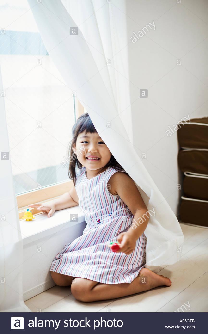 Maison de famille. Une fille jouant par une fenêtre, se cacher derrière le rideau. Photo Stock