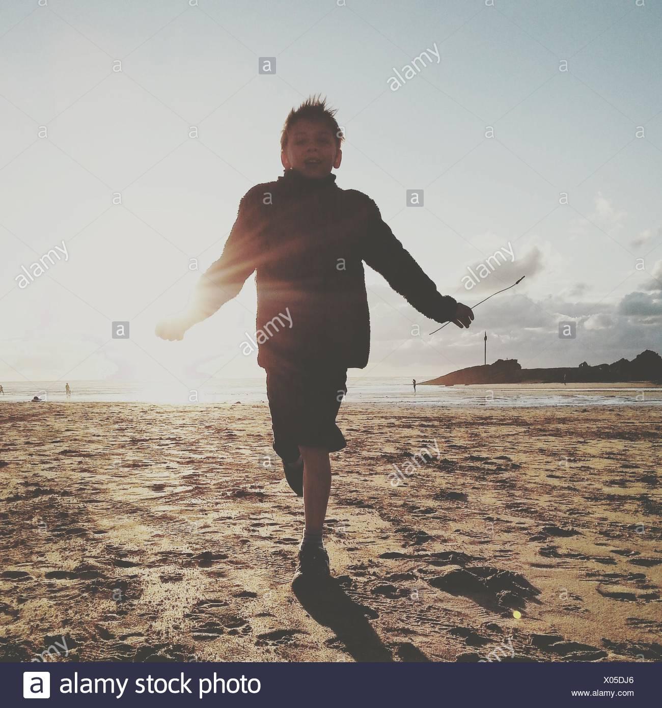 Low Angle View Of Boy Running On Beach contre ciel lors de journée ensoleillée Photo Stock