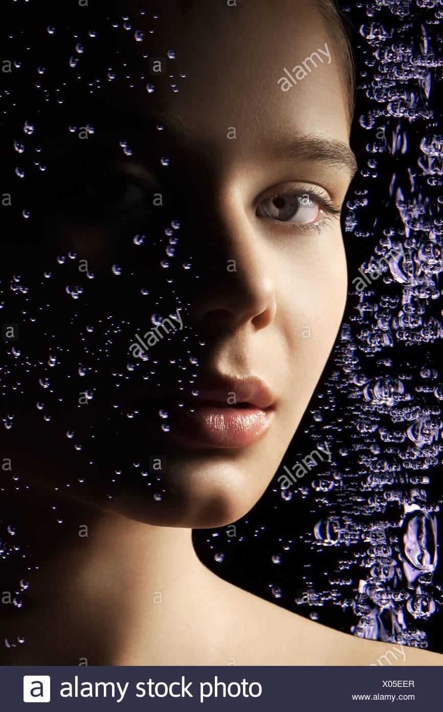 Le visage d'une femme derrière une fenêtre couverte de gouttelettes d'eau Photo Stock