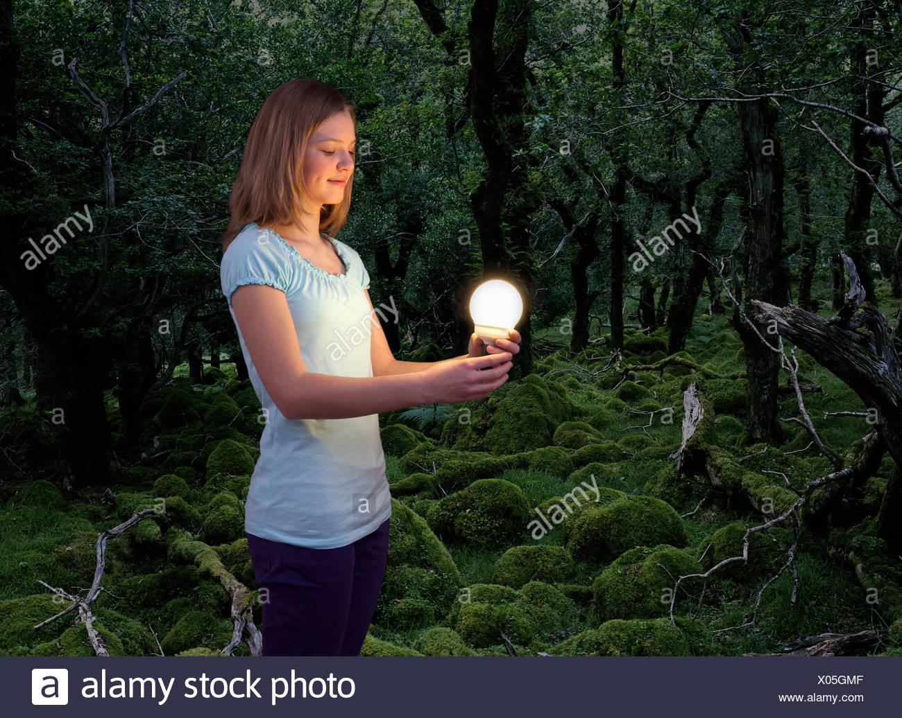 Fille avec ampoule à économie d'énergie Photo Stock