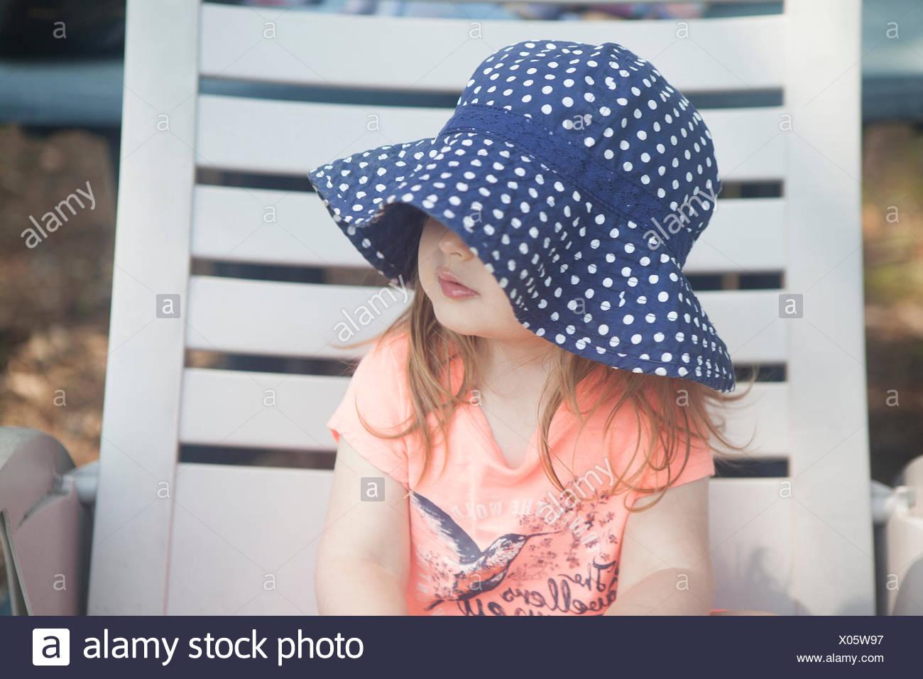 Fille assise sur une chaise longue Photo Stock