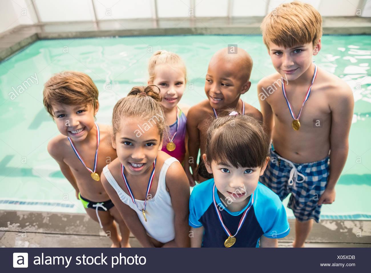 Cours de natation piscine mignon souriant avec des médailles Photo Stock
