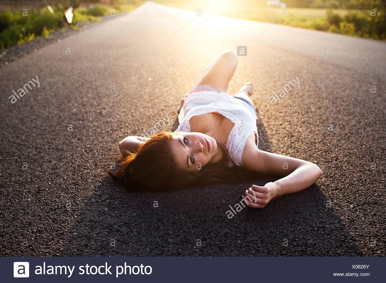 Une fille se trouve sur la route au coucher du soleil dans l'Idaho. Photo Stock
