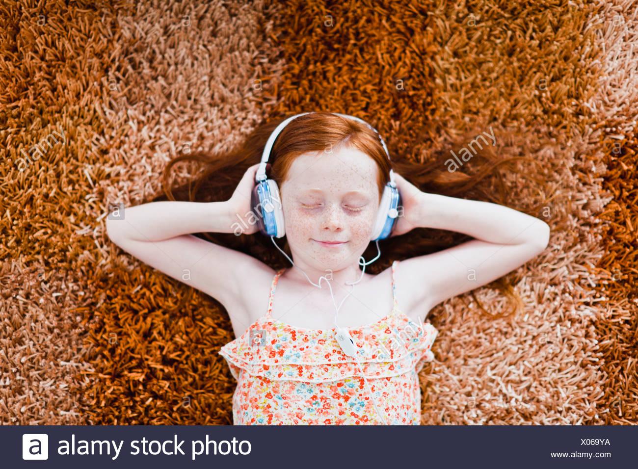 Girl listening to headphones on carpet Photo Stock