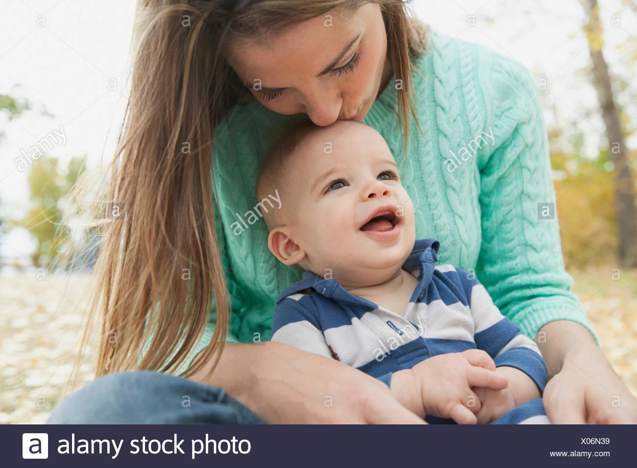 Mère embrassant fils tête à park Photo Stock