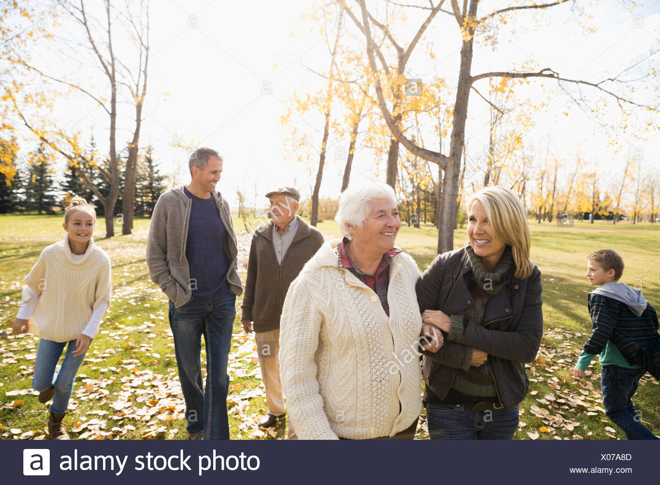 Multi-generation family walking in sunny autumn park Banque D'Images